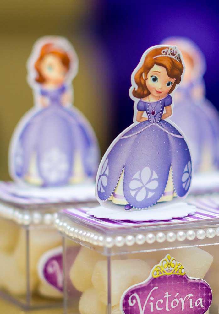 Para decorar a caixinha de guloseimas, use pérolas, adesivos personalizados e uma bonequinha de papel no formato da Princesa Sofia.