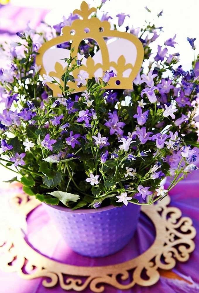Prepare vasos com lindos arranjos florais. Para combinar ainda mais com a decoração, coloque coroas para enfeitar.