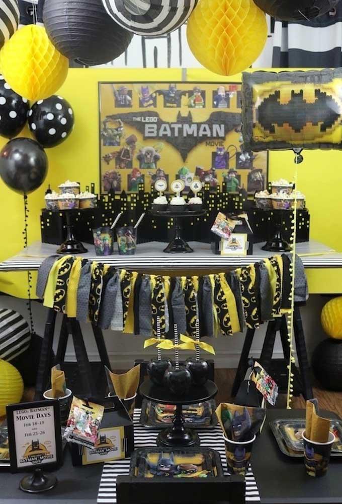 Que tal reproduzir Gotham City na mesa principal do aniversário? Para isso, use e abuse das cores preta e amarela para destacar todos os elementos da festa.
