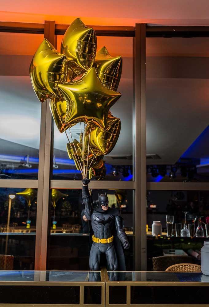 Vamos colocar o Batman para animar a festa? Pendure alguns balões metálicos no braço do boneco.