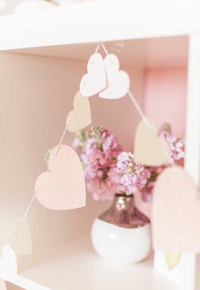 Corte vários corações para fazer uma decoração dia dos namorados com papel.