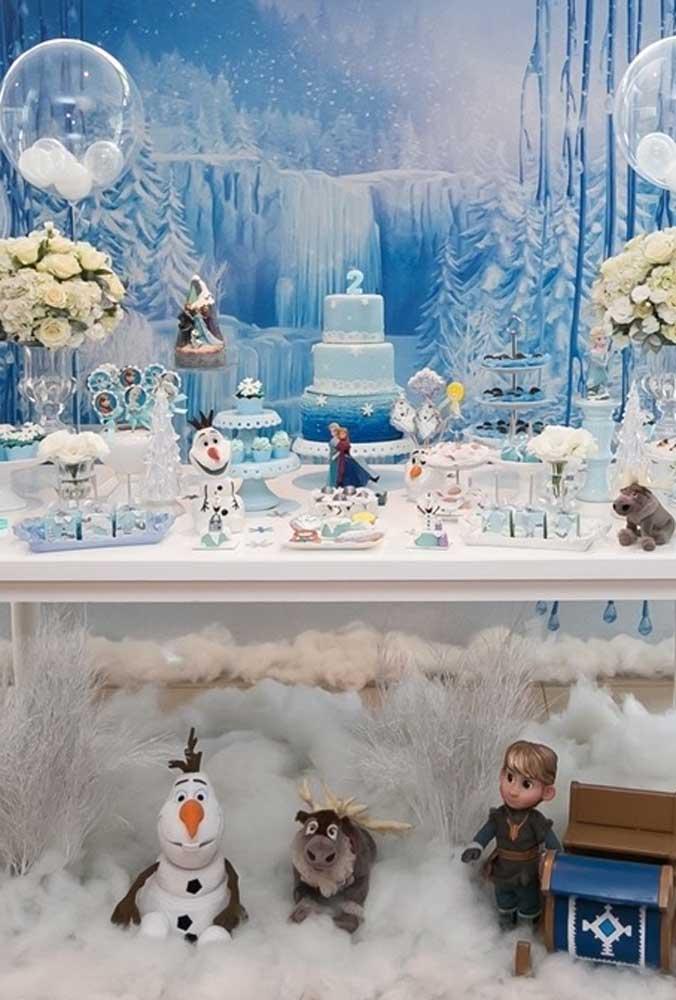O grande destaque dessa decoração de festa Frozen é o painel aos fundos com o cenário de neve