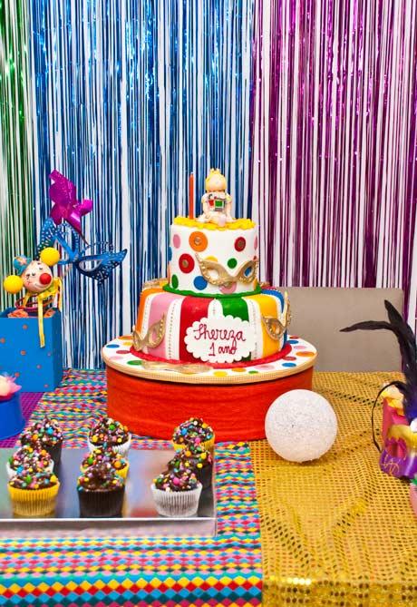 Um bolo com máscaras, bolinhas e muita cor