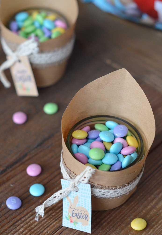 Encha um pote transparente com guloseimas e decore com papel reciclado e fita.