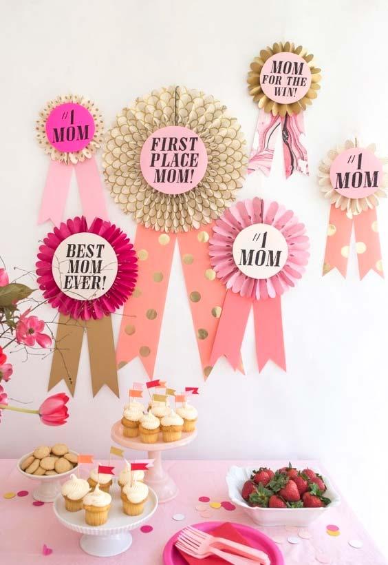 Medalhas e fitas de melhor mãe do mundo decorando a parede da mesa de comes