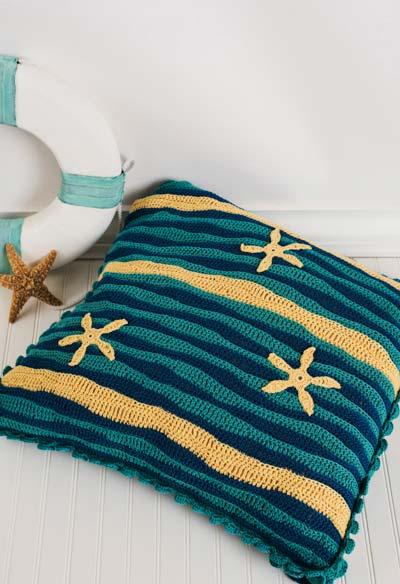 Uma almofada de crochê com motivos praianos