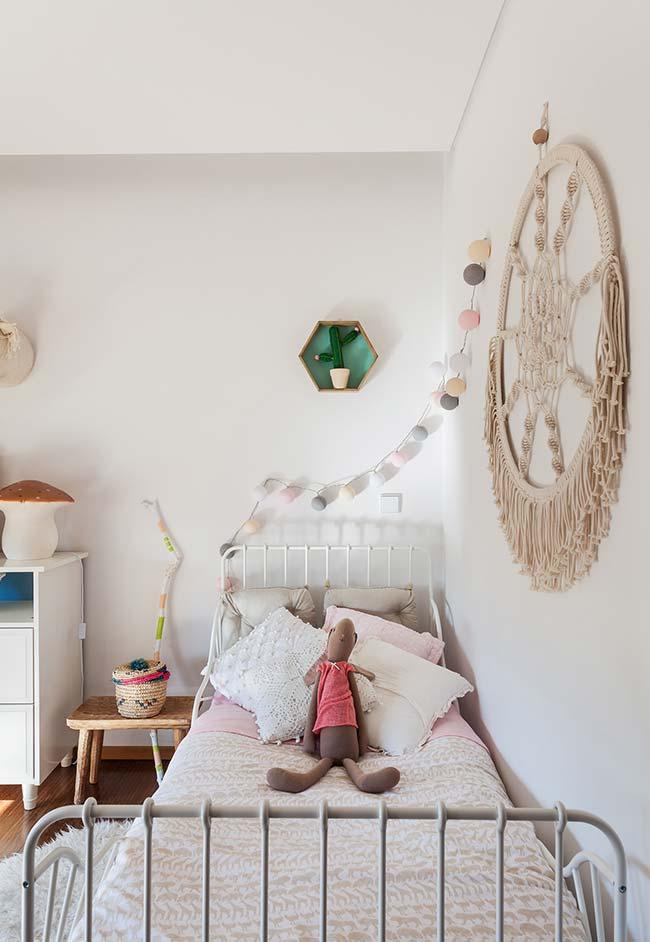Quartinho infantil com várias almofadas sobre a cama, uma delas de crochê