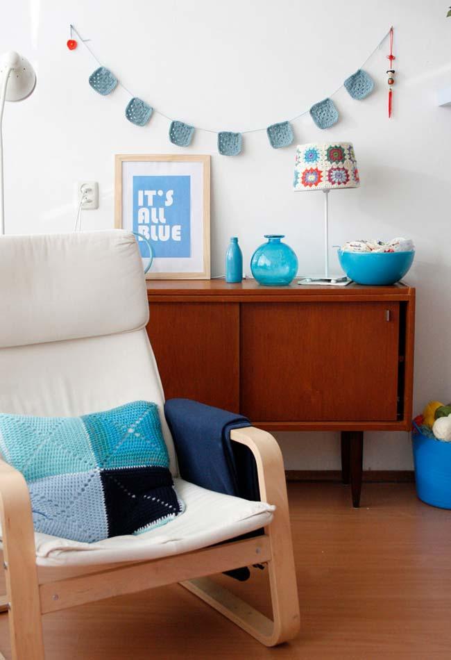 Quatro quadrados azuis na almofada de croche