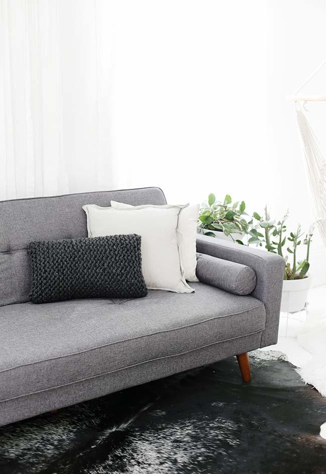 Sala com decoração neutra e almofada de crochê preta