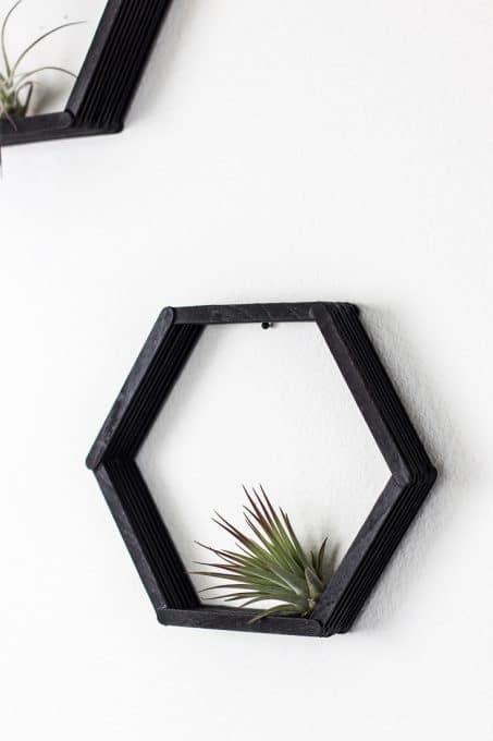 Palitos pintados de preto no enfeite de parede