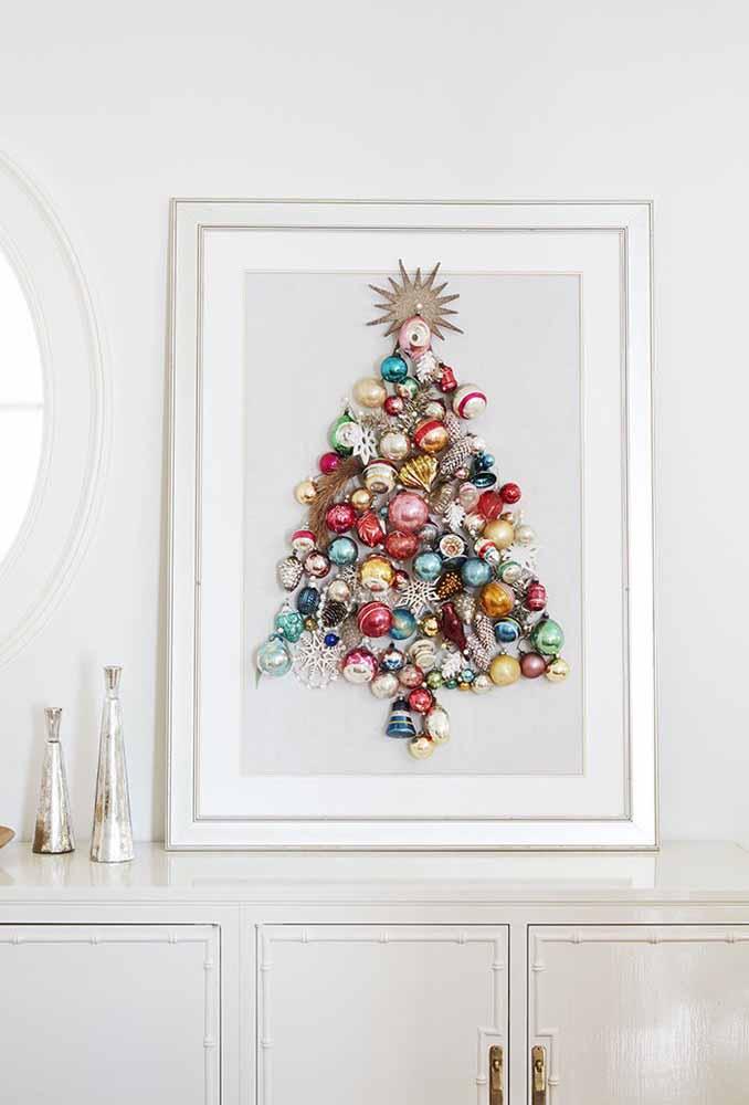 Junte vários itens decorativos de natal e monte uma árvore para colocar em um quadro