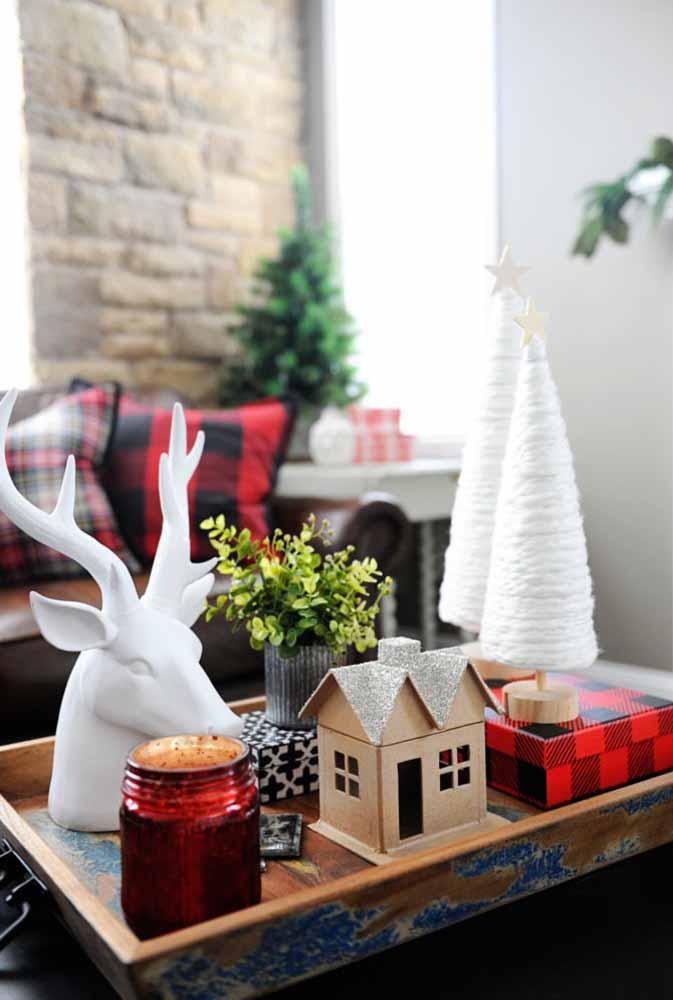 Reúna vários itens natalinos, coloque em uma bandeja e enfeite a mesinha de centro da sala