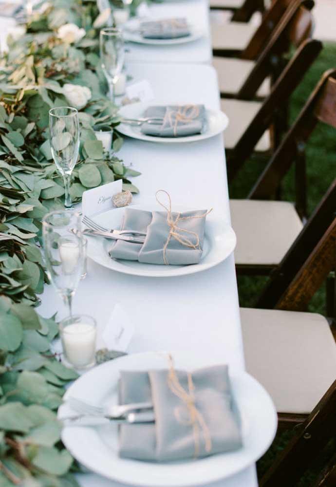 Faça uma decoração com folhas para colocar em cima da mesa de jantar e coloque os talheres dentro de um tecido amarrado por um fio.