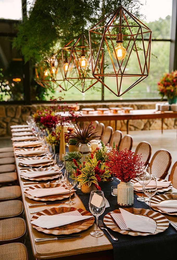 Capriche na decoração das mesas dos convidados. Use vários arranjos de flores no espaço central e invista em luminárias pendentes.