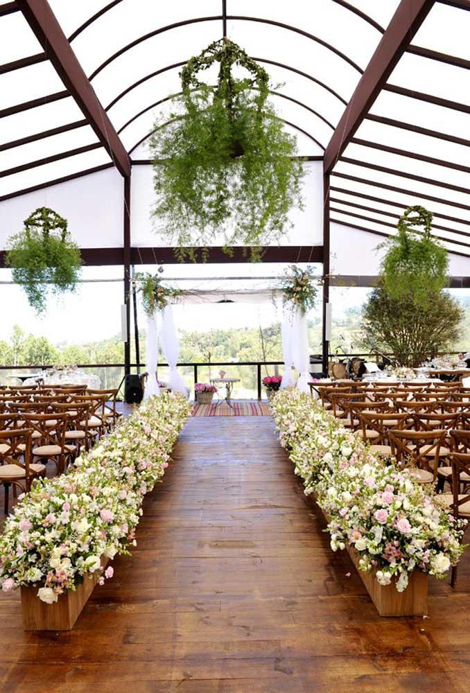 Na decoração do espaço da cerimônia, os arranjos florais entre os bancos são o grande destaque do ambiente.