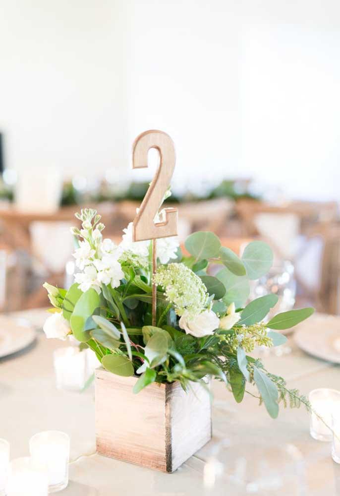 Uma boa ideia é identificar todas as mesas dos convidados. Para isso, use um vaso feito de madeira com flores e coloque um número de identificação também feito de madeira.