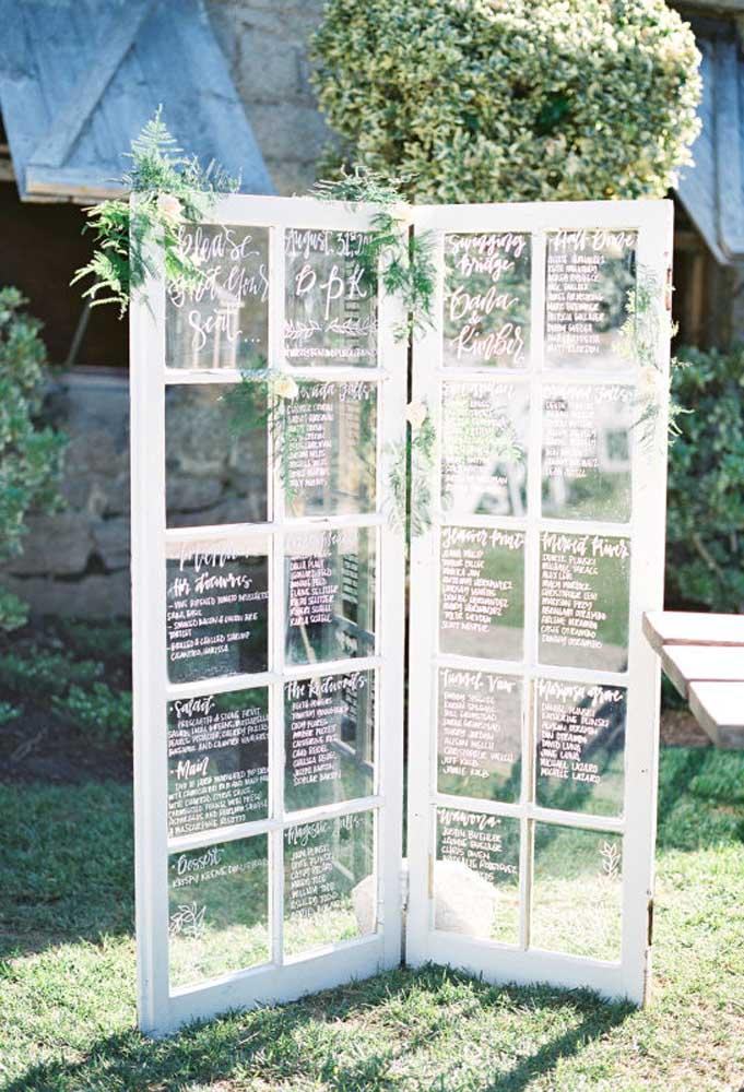 Uma porta antiga feita de madeira e vidro pode servir como objeto de decoração de um casamento rústico.