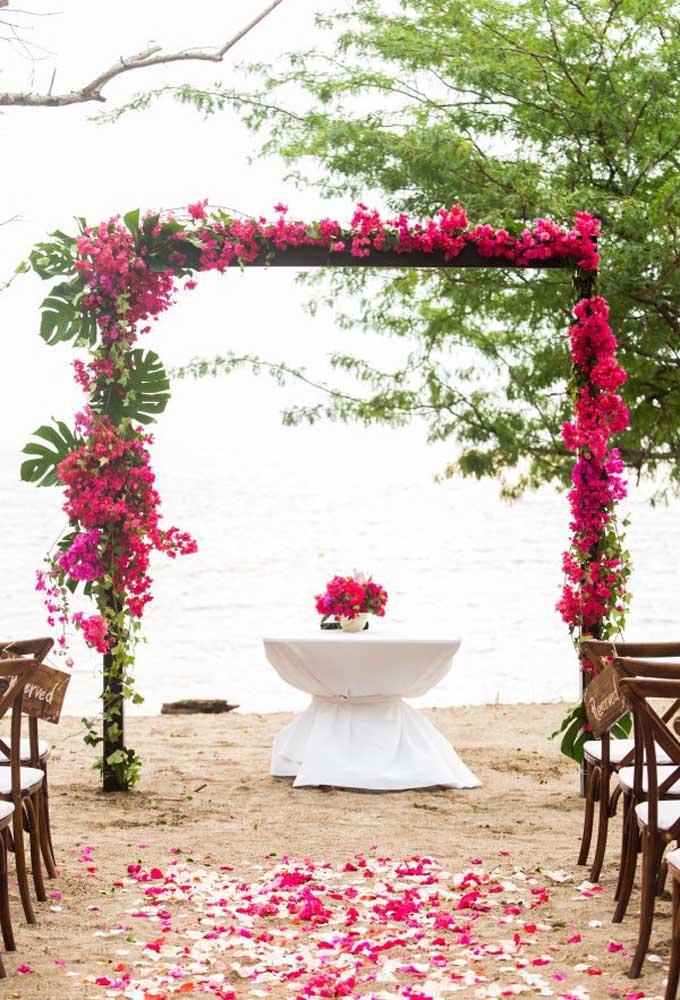 Uma excelente opção para identificar e decorar o altar de um casamento na praia é usar arcos com arranjos florais.