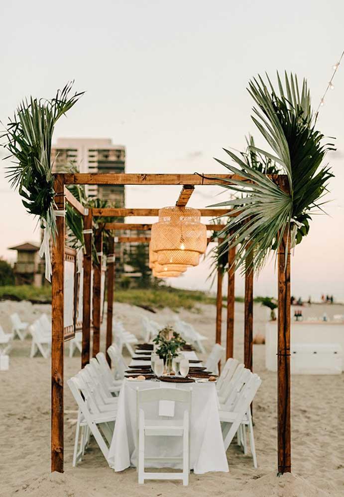 Separe a mesa que os noivos vão sentar e decore com armações de madeira, arranjos com folhas e plantas e belas luminárias.