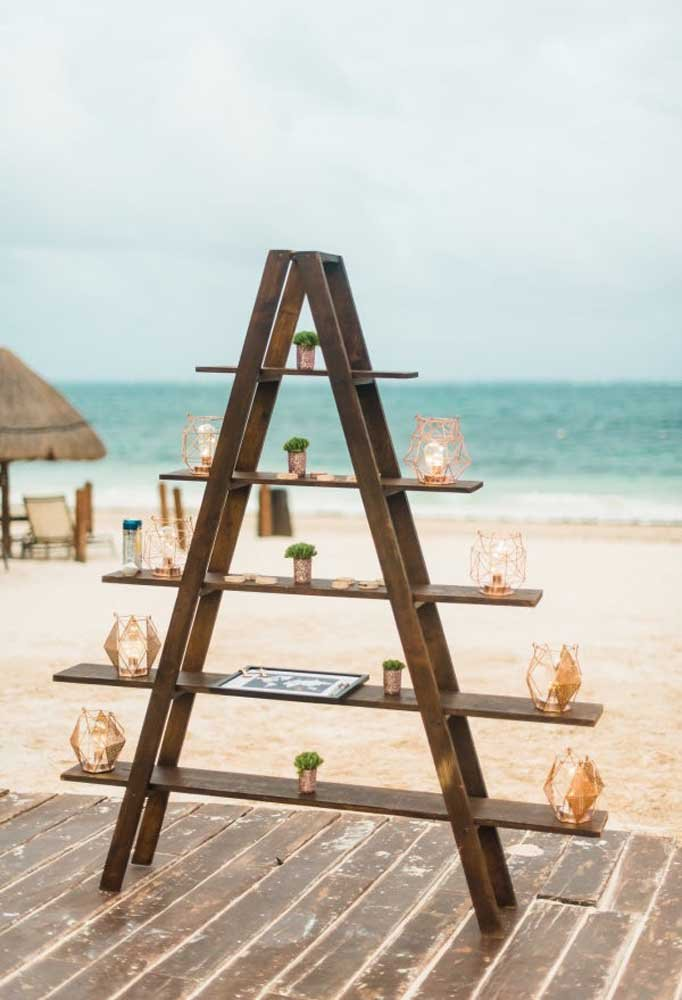 Para decorar um casamento na praia, o ideal é usar móveis simples feitos com madeira. Nele você pode colocar algumas luminárias e vasos de flores.