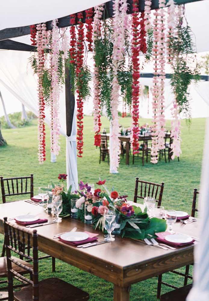 Uma boa opção para decorar as mesas dos convidados é usar arranjos de flores tanto no centro da mesa quanto pendurados na estrutura que fica em cima da mesa.