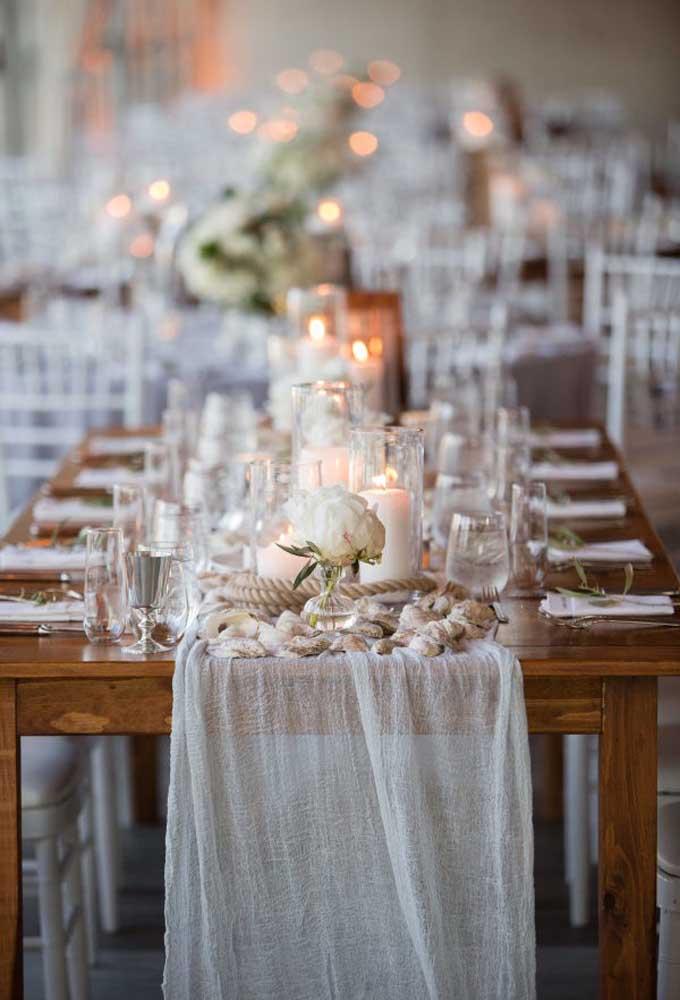 Para um casamento mais intimista, decore a mesa com tecido, copos com velas e alguns arranjos com flores, sempre priorizando a tranquilidade da cor branca.