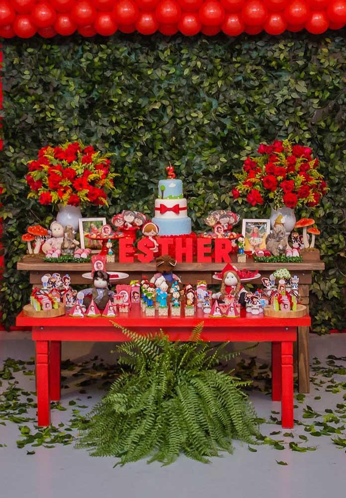 Quer caprichar na decoração com o tema Chapeuzinho Vermelho? Faça um painel com folhas artificiais, prepare alguns arranjos com flores vermelhas e encha a mesa com vários elementos decorativos.